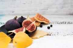 切片在一块板材、曲奇饼和莓果的被切的无花果在明亮的模糊的背景,与黄色叶子 库存图片