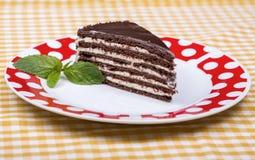 切片在一块白色板材的富有的潮湿巧克力蛋糕有层数的 餐馆烹调 库存图片