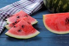 切片在一张蓝色木桌上的成熟西瓜和一个整个西瓜在背景中 免版税库存图片