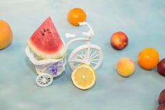 切片在一辆装饰自行车的西瓜用在蓝色背景带来的果子 免版税库存图片