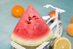 切片在一辆装饰自行车的西瓜用在蓝色背景带来的果子 免版税库存照片