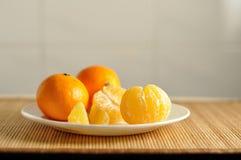 切片在板材的未加工的橙色蜜桔 图库摄影