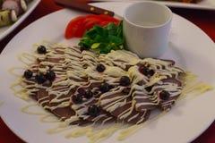 切片在板材的牛舌肉,装饰用蛋黄酱和橄榄 免版税库存照片