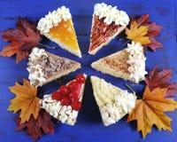 切片在深蓝木头的感恩饼与秋叶 免版税库存照片