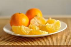 切片在白色板材的未加工的橙色蜜桔 免版税图库摄影