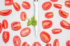 切片在白色背景的红色成熟蕃茄在厨房 在一半划分的蕃茄,窃取在中心的刀子 库存照片