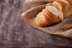 切片在粗麻布在黑暗的木桌上,文本的空间的白面包 免版税库存图片