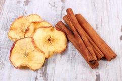 切片在老土气木背景的干苹果和肉桂条 图库摄影