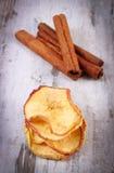 切片在老土气木背景的干苹果和肉桂条 库存照片
