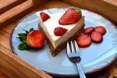 切片在蓝色板材的未加工的草莓蛋糕 免版税库存图片