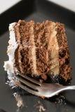 切片在黑色的盘子的巧克力蛋糕有金属叉子的 库存图片