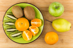 切片在绿色板材的各种各样的果子在桌上 免版税图库摄影