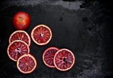 切片在黑金属背景的红色桔子 免版税图库摄影