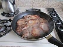 切片在黑长柄浅锅的肉有出来的蒸汽的 免版税库存照片