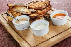 切片多士在一个木板的一个调味汁烤了添面包用乳酪和滑倒 免版税库存图片