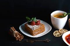 切片层状蜜糕装饰用草莓,点心叉子,薄菏,烘干了柠檬,桂香,草莓酱,杯子o棍子  免版税库存图片