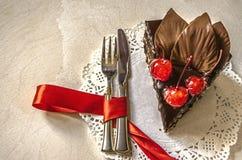 切片巧克力蛋糕用樱桃和叶子在一块白色餐巾与叉子 免版税库存图片