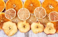 切片干柠檬、桔子和苹果在老木背景 免版税库存照片