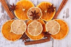 切片干柠檬、桔子和香料在老木背景 图库摄影