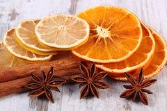 切片干柠檬、桔子和香料在老木背景 库存图片
