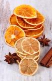 切片干柠檬、桔子和香料在老木背景 免版税库存图片