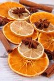 切片干柠檬、桔子和香料在老木背景 免版税库存照片