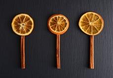 切片干桔子与和在黑暗的背景的桂香香料 免版税库存照片