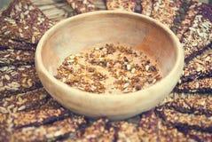 切片或健康,未加工的谷物酥脆面包与坚果,种子和香料在木板 库存图片