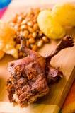切片断说谎木表面上的煮熟的guine猪肉在土豆、tostados和碗辣调味汁旁边 免版税库存照片