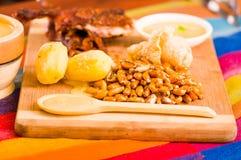 切片断说谎木表面上的煮熟的guine猪肉在土豆、tostados和碗辣调味汁旁边 免版税库存图片