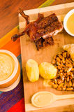 切片断说谎木表面上的煮熟的guine猪肉在土豆、tostados和碗辣调味汁旁边 库存照片