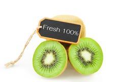 切片新鲜的猕猴桃和新鲜的100%木标记 免版税库存照片
