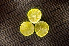 切片柠檬或石灰在黑背景与条纹 免版税库存图片