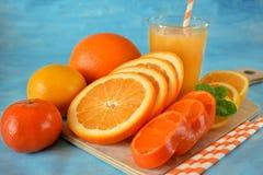 切片桔子、普通话和柠檬和黄色汁液 免版税库存照片
