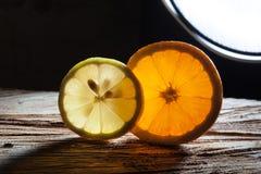 切片桔子和柠檬概略的木表面上 免版税库存照片