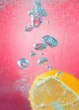 切片桔子在水中与泡影,在红色背景 免版税库存照片