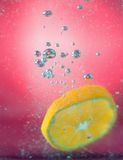 切片桔子在水中与泡影,在红色背景 库存图片