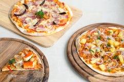 切片海鲜意大利薄饼和夏威夷鸡BBQ意大利薄饼和烟肉、大蒜和辣椒意大利薄饼在木盘 免版税库存图片