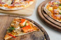 切片海鲜意大利薄饼和夏威夷鸡BBQ意大利薄饼和烟肉、大蒜和辣椒意大利薄饼在木盘 库存图片