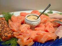 切片熏制鲑鱼在有油煎的三文鱼内圆角、莳萝和一个小瓷盘的一块板材安排了用芥末酱 免版税图库摄影