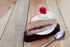 切片牛奶蛋糕用在木纹理投入的樱桃 库存图片