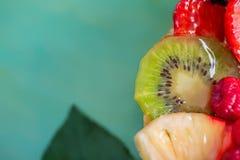 切片猕猴桃和各种各样的新鲜水果在甜明胶 莓果特写镜头在软的焦点 o 库存图片