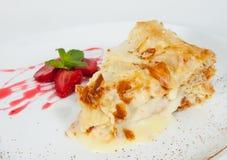 切片用草莓拿破仑蛋糕装饰,服务在白色板材 免版税库存照片