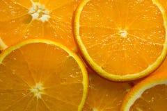 从切片的明亮的橙色背景水多的桔子 免版税库存照片
