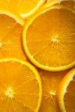 从切片的明亮的橙色背景水多的桔子 免版税图库摄影