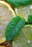 切片石灰和薄菏柠檬、叶子和蔗糖 免版税库存照片