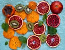 切片红色桔子、猕猴桃和柿子在纸背景col 免版税库存图片