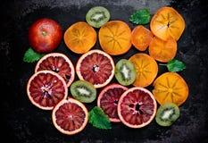 切片红色桔子、猕猴桃和柿子在黑金属backg 免版税库存照片
