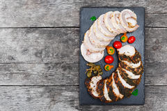 切片自创肉饼、小牛肉和用在黑板岩的菜充塞的猪里脊肉向在木背景的黑板扔石头 免版税图库摄影