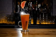 切片葡萄柚落入与酒精鸡尾酒的一块玻璃 图库摄影